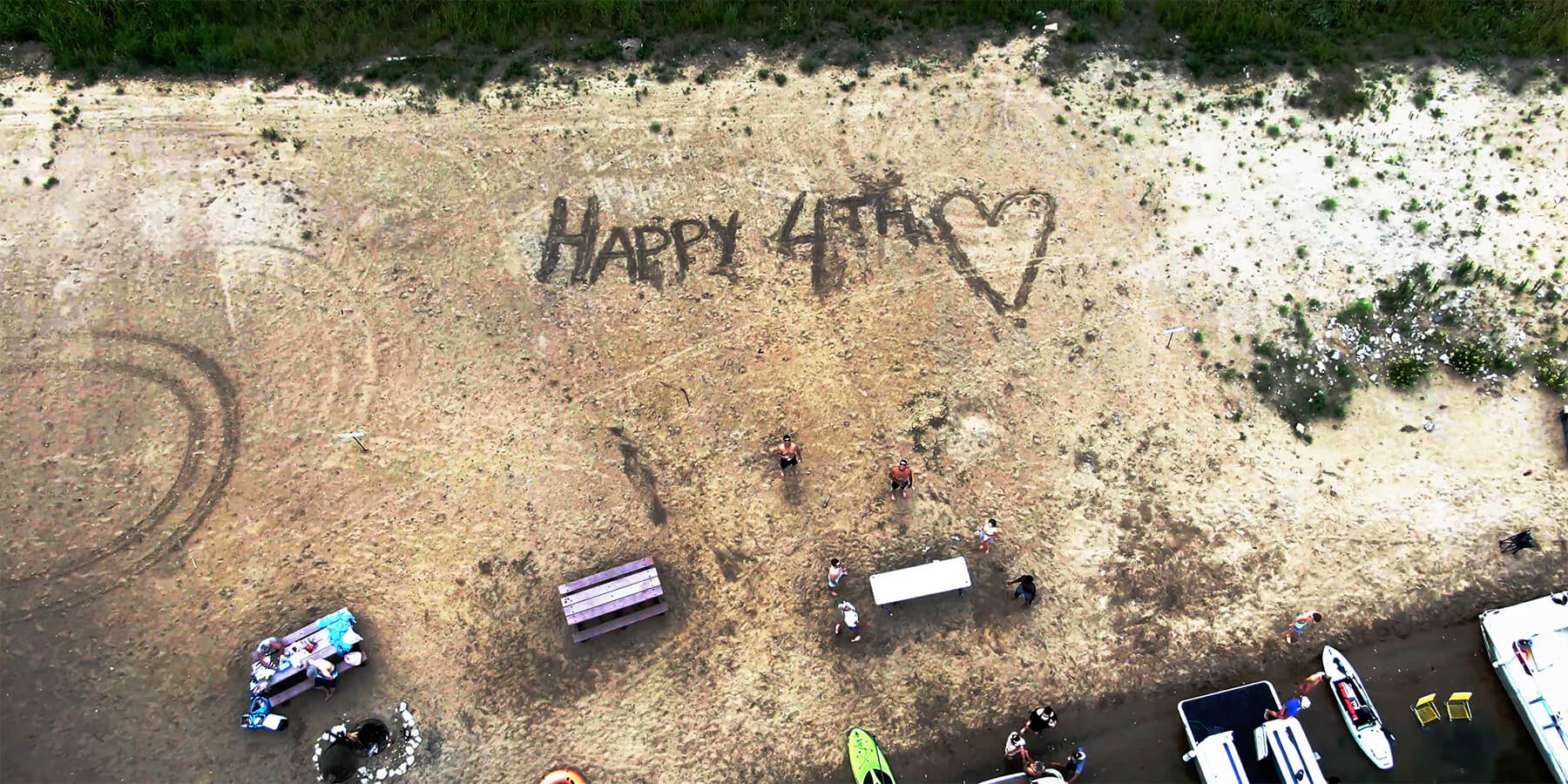 Drone Footage of Beach with Happy 4th Written in the Sand