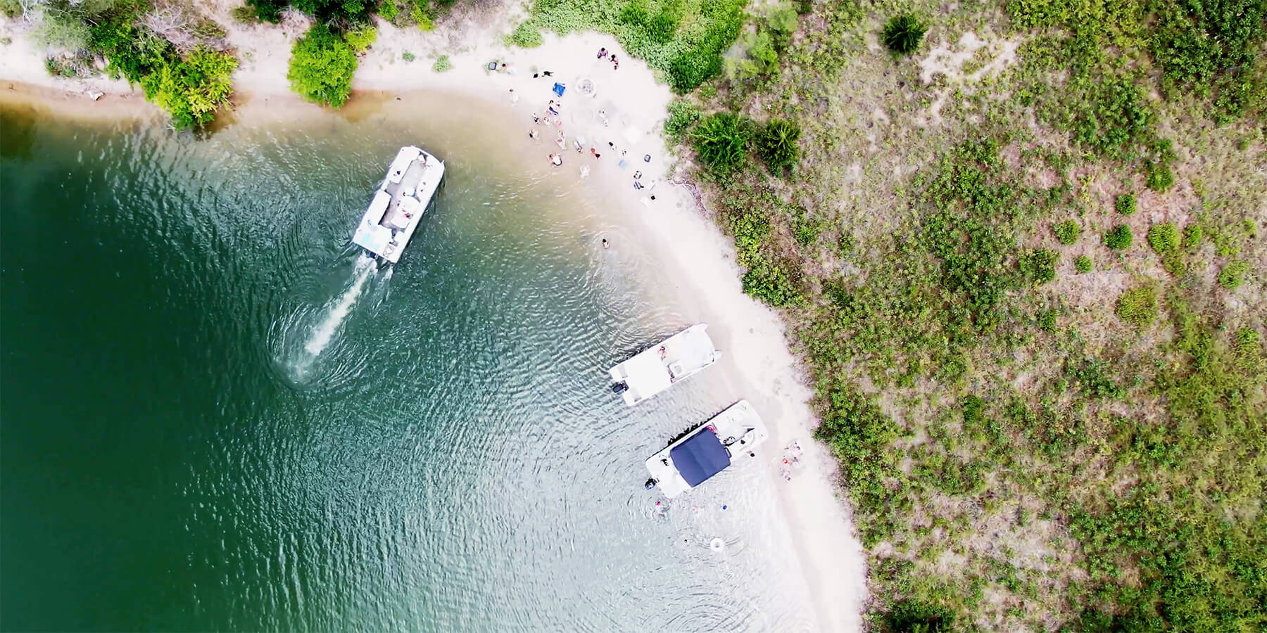 Aerial view of pontoon boat pulling up to beach with people.