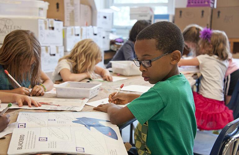 Elementary School Aged Children Working in Workbooks at Table