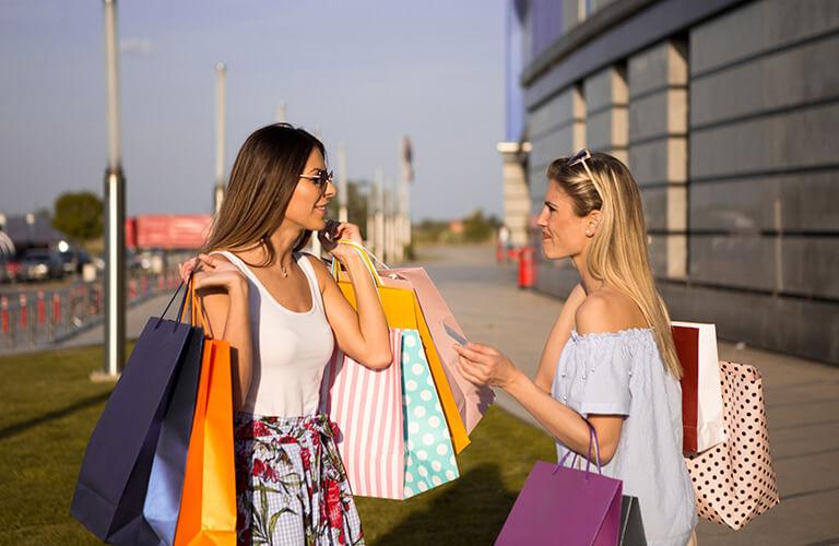 Two Women Holding Shopping Bags Talking
